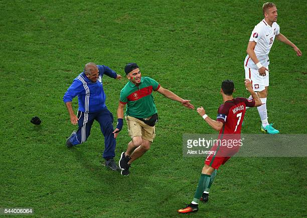 An invading fan tries to hug Cristiano Ronaldo of Portugal during the UEFA EURO 2016 quarter final match between Poland and Portugal at Stade...