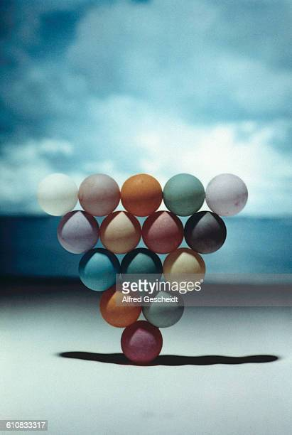 An inverted triangle of coloured balls on a beach 1984