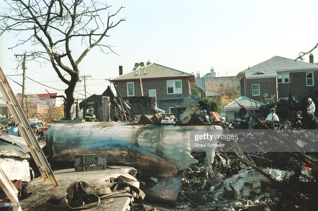 An investigator examines the wreckage of American Airlines flight 587 among  destroyed houses November 13 2001