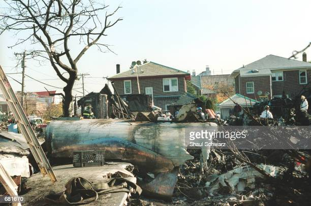 An investigator examines the wreckage of American Airlines flight 587 among destroyed houses November 13 2001 in the Rockaway section of Queens New...