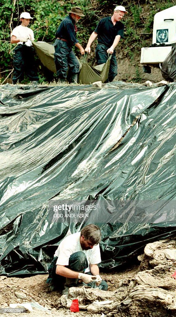 An investigator for the UN International Crimes Tribunal for ex-Yugoslavia examines human remains in a mass grave outside the village of Cerska, near Srebrenica, some 40 miles southeast of Tuzla in the Serb entity 15 July 1996 while others (rear) remove a body from the site. After ten consecutive days of work, investigators expected to finish removing some 60 bodies uncovered earlier before moving to another site nearby.