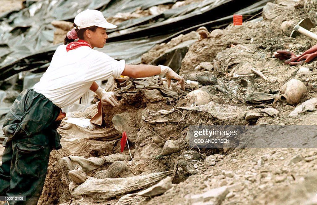 An investigator for the UN International Crimes Tribunal for ex-Yugoslavia removes earth from bodies in a mass grave outside the village of Cerska, near Srebrenica, Bosnia, 40 miles (65 km) southeast of Tuzla in the Serb entity 15 July 1996. After 10 days of work at the site, investigators expected to finish removing 60 bodies uncovered earlier before moving to another site nearby. Bosnian Serb forces executed up to 8,000 Moslems in their capture of the UN 'safe haven' of Srebrenica in July 1995. AFP PHOTO/Odd ANDERSEN