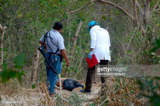 An investigator of the prosecution office and a policeman work at the crime scene next to a man's corpse in the outskirts of Acapulco, Guerrero...
