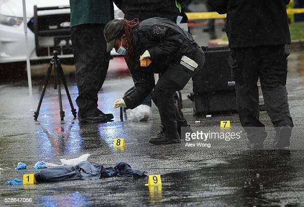 An investigator picks up a shell casing that was left behind at a shooting crime scene at Westfield Montgomery Mall May 6 2016 in Bethesda Maryland...