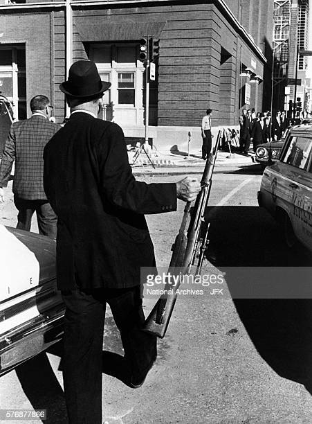An investigator removes from the Texas School Book Depository the rifle allegedly used to assassinate President Kennedy