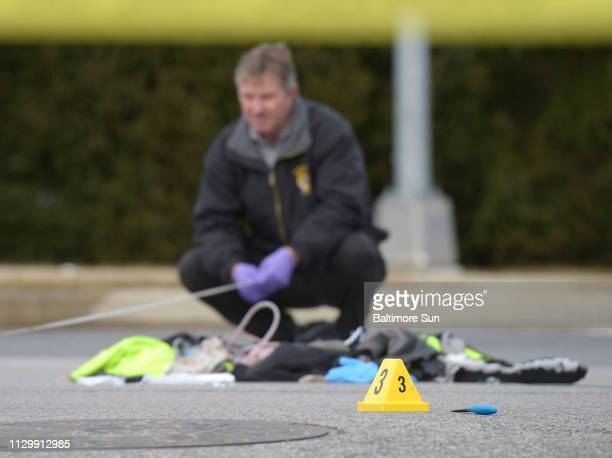 An investigator takes measurments at the scene of a police-involved shooting where a state trooper was reportedly stabbed in the 500 Block of...
