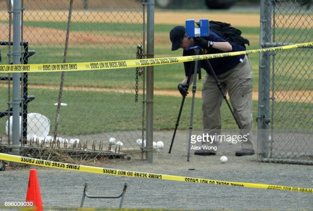 An investigator uses an equipment to survey at the site of this morning's shooting at Eugene Simpson Stadium Park June 14 2017 in Alexandria Virginia...