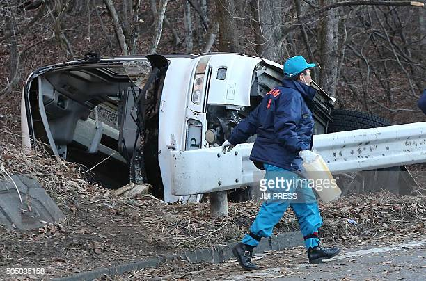 An investigator walks beside the wreckage of a bus which crashed after running off a road in Karuizawa Nagano prefecture on January 15 2016 Fourteen...