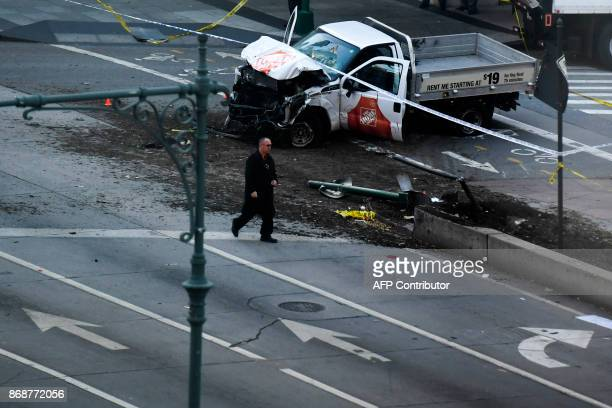 An investigator walks past a crashed pickup truck following an incident in New York on October 31 2017 A pickup driver killed eight people in New...
