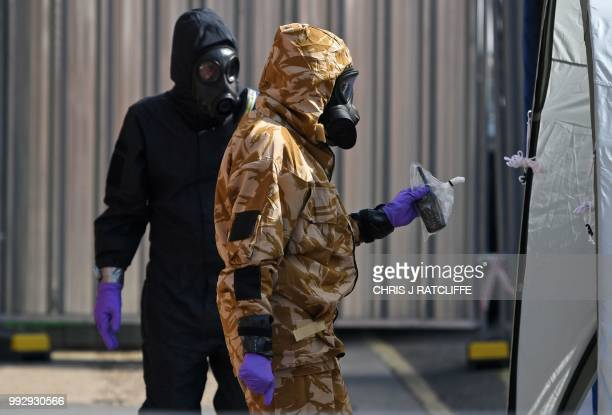 An investigator wearing a camouflaged protective suit gloves and a gas mask works with a police investigator in a protective suit in Rollestone...