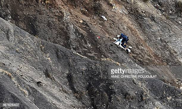 An investigator works on March 26 2015 on scattered debris on the crash site of the Germanwings Airbus A320 that crashed in the French Alps above the...