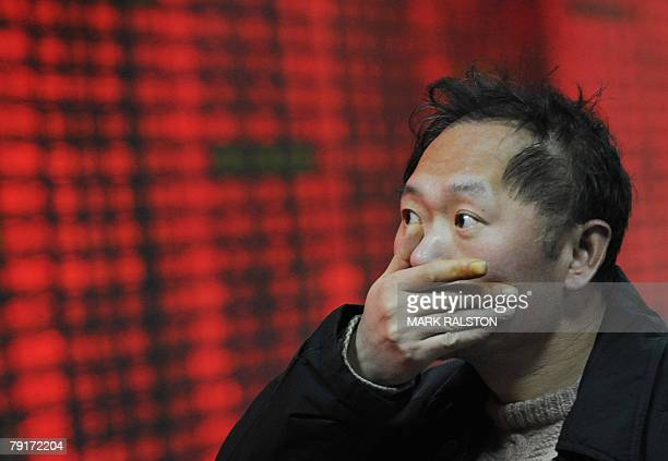 An investor gestures in front of a stock price board showing the red colour indicating rising prices at a private securities firm in Shanghai 23...