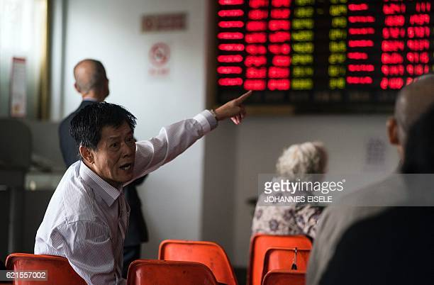 An investor gestures in front of the stock price movements on a screen at a securities company in Shanghai on November 7 2016 / AFP / JOHANNES EISELE