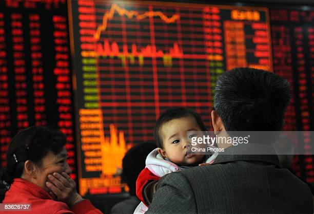 An investor holding his child views stock prices at a securities company on November 10 2008 in Wuhan of Hubei Province China The benchmark Shanghai...