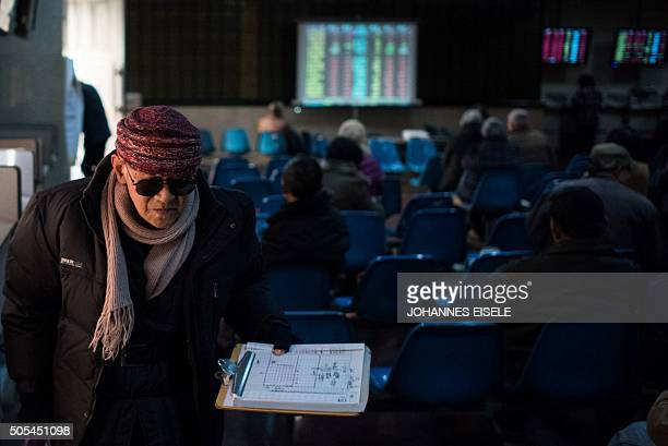 An investor is seen as others look at an electronic board showing stock information at a brokerage house in Shanghai on January 18 2016 Shanghai...