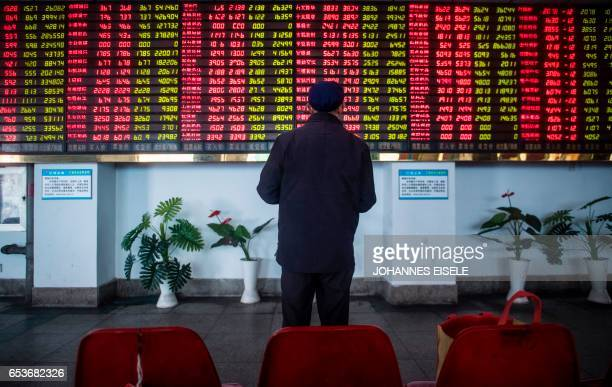 TOPSHOT An investor looks at an electronic board showing stock information at a brokerage house in Shanghai on March 16 2017 / AFP PHOTO / Johannes...