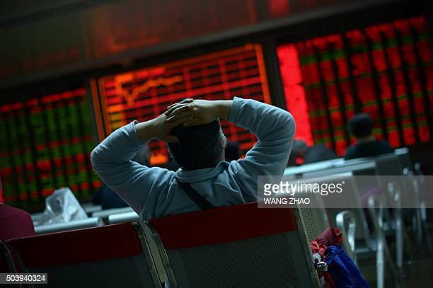 TOPSHOT An investor looks at screens showing stock market movements at a securities company in Beijing on January 8 2016 Chinese equities led another...