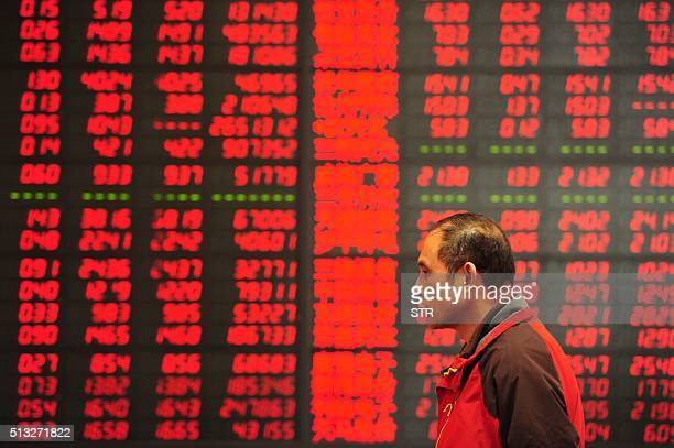 An investor makes his way in front of a screen showing stock market movements in a securities firm in Fuyang east China's Anhui province on March 2...