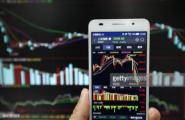 An investor observes the stock market on his phone at an exchange hall on January 13 2016 in Huaibei Anhui Province of China The Chinese stock market...