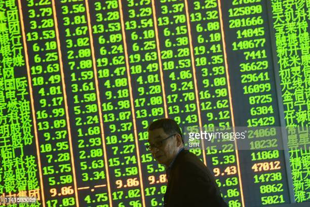 An investor reacts in front of a stock price board showing the green colouring which indicates falling prices at a securities company in Hangzhou in...