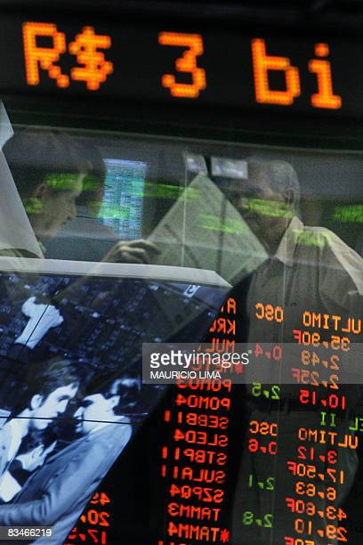 An investor reads a newspaper as another follows on a monitor share values of Brazilian companies at the Sao Paulo Stock Exchange in Sao Paulo Brazil...