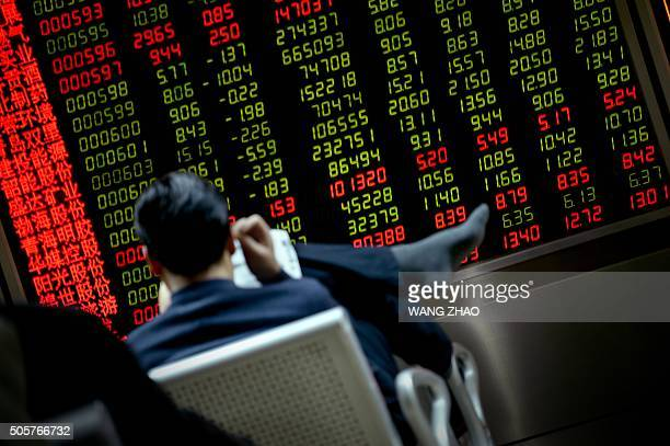 An investor reads a newspaper in front of a screen showing stock market movements at a securities company in Beijing on January 20 2016 Asian markets...