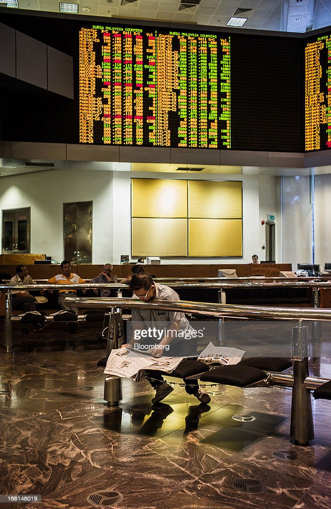 An investor reads a newspaper in the trading gallery at the RHB Investment Bank Bhd. headquarters in Kuala Lumpur, Malaysia, on Monday, May 6, 2013. The biggest surge in Malaysian stocks since 2008 has turned into a money-losing day for investors who piled in at the height of the rally sparked by Prime Minister Najib Razak's election victory. Photographer: Sanjit Das/Bloomberg via Getty Images