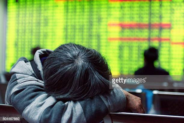 An investor rests in front of a screens showing stock market movements at a securities firm in Hangzhou in eastern China's Zhejiang province on...