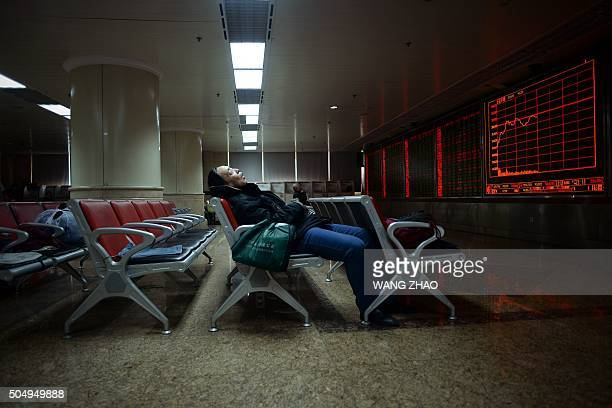TOPSHOT An investor rests on a chair in front of screens showing stock market movements at a securities company in Beijing on January 14 2016...