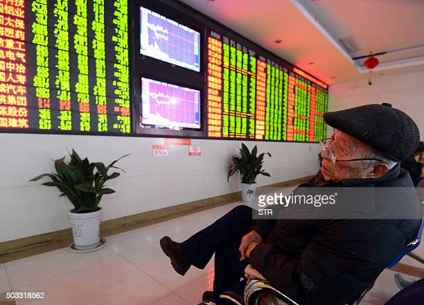 An investor sits in front of a screen showing stock market movements in a stock firm in Fuyang east China's Anhui province on January 4 2016 Trading...