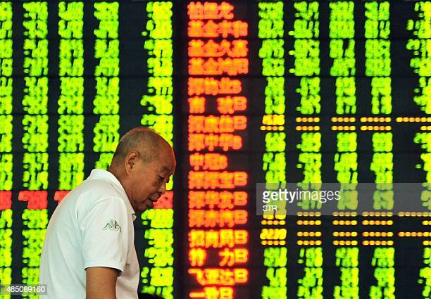 An investor stands in front of a screen showing share prices at a securities firm in Hangzhou in eastern China's Zhejiang province on August 24 2015...