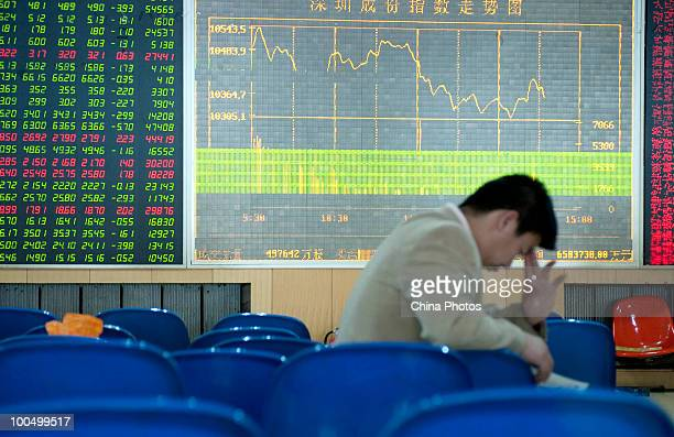An investor take a nap as he views stock prices at a securities company on May 25, 2010 in Changchun of Jilin Province, China. The Shanghai Composite...
