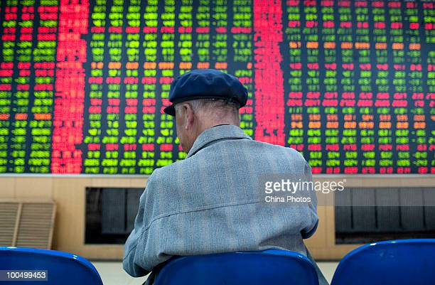 An investor takes a nap as he views stock prices at a securities company on May 25, 2010 in Changchun of Jilin Province, China. The Shanghai...