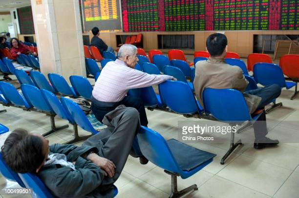 An investor takes a nap as others view stock prices at a securities company on May 25, 2010 in Changchun of Jilin Province, China. The Shanghai...