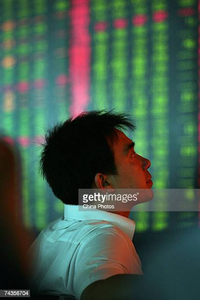 An investor views the stock index at a securities company on May 30 2007 in Nanjing China The Shanghai Composite Index fell by 65% today after stamp...