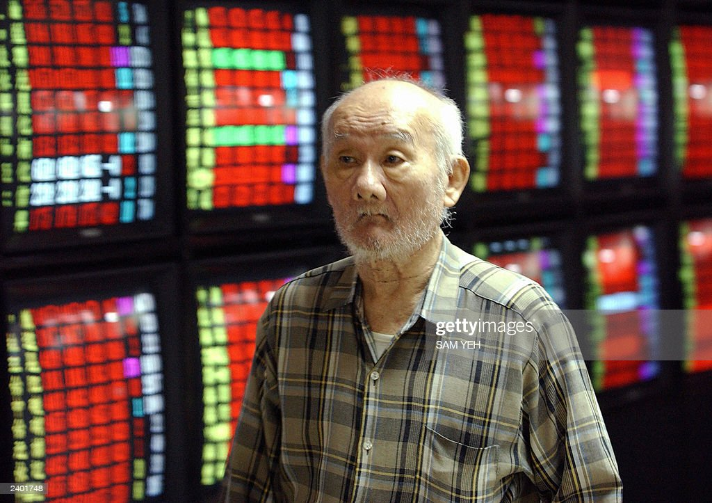 An investor walks past the monitors show : News Photo