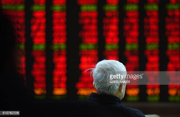 An investor watches stock movements on a screen at a securities company in Beijing on February 17 2016 The Shanghai market rose more than one percent...