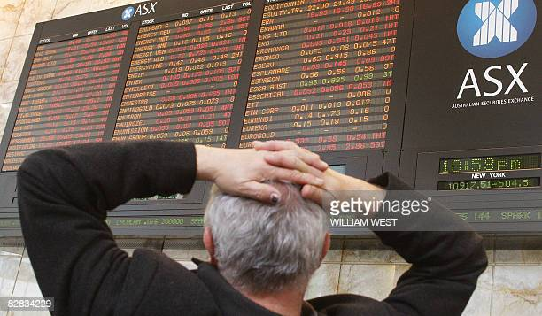 An investor watches the Australian Stock Exchange board in Melbourne showing the sharemarket with heavy losses as investors pummelled Australia's...