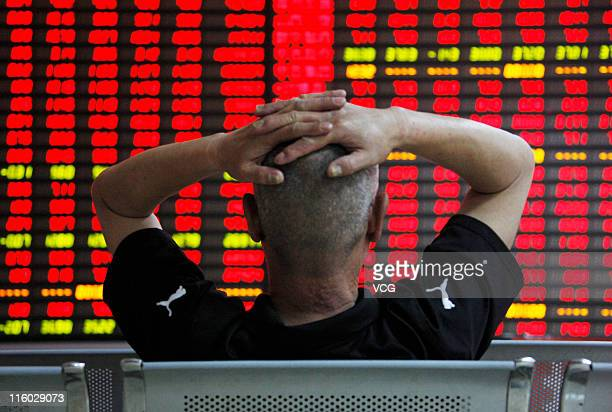 An investor watches the electronic board at a stock exchange hall on June 14, 2011 in Huaibei, Anhui Province of China. International markets have...