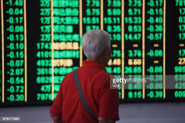 An investor watches the electronic board at a stock exchange hall on June 19 2018 in Hangzhou China Chinese shares plunged on Tuesday with the...
