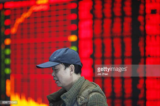 An investor watchs the electric board in a stock market in Huaibei, Anhui province, east China on 14th March 2016.The Shanghai Composite Index...