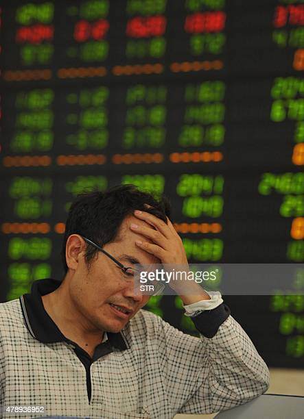 An investors checks share prices in a stock firm in Fuyang east China's Anhui province on June 29 2015 Chinese shares plunged in morning trading on...