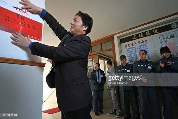 An invigilator pastes a test room label as foreign inmates wait to attend the Hanyu Shuiping Kaoshi test at the Shanghai Qingpu Prison on December 10...