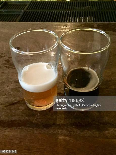 an ipa and a stout: two tall glasses of different beer with varying texture and taste - help:ipa stock pictures, royalty-free photos & images