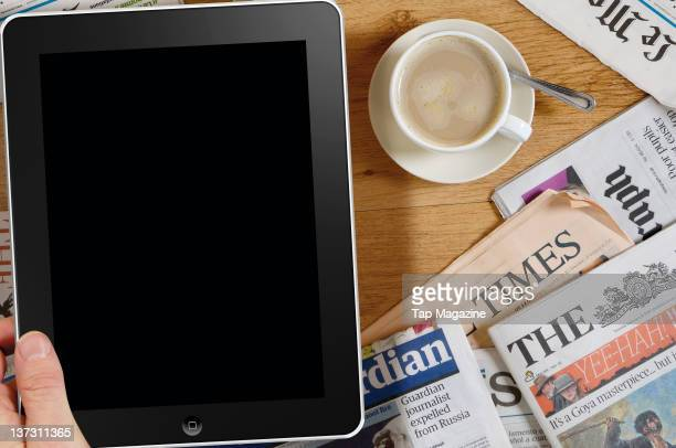 An iPad on a table with coffee and newspaperse February 8 2011
