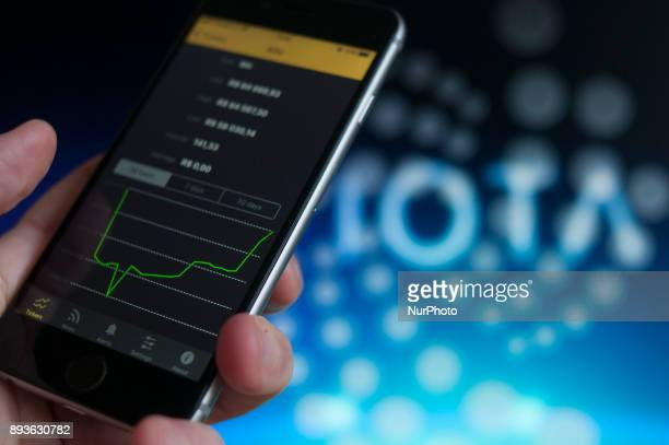 An iPhone is seen with a bitcoin price graph and the logo of the new IOTA currency in the background in this photo illustration on December 15 2017...