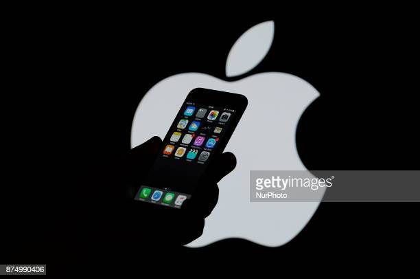 An iPhone is seen with an Apple logo in the background in this photo illustration on November 15 2017