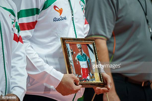TOPSHOT An IR Iran's player holds a portrait of Para cyclist Bahman Golbarnezhad IRI who died competing the previous day at their Men's Gold Medal...