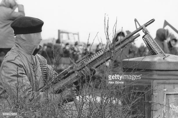 An IRA gunman holds a USmade M60 machine gun and wears a stocking as a disguise during a demonstration in the Republican Creggan estate in...