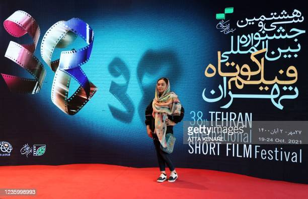An Iranian arrives for the opening day of the 38th Tehran International Short Film Festival in the Iranian capital on October 19, 2021 . - Tehran's...